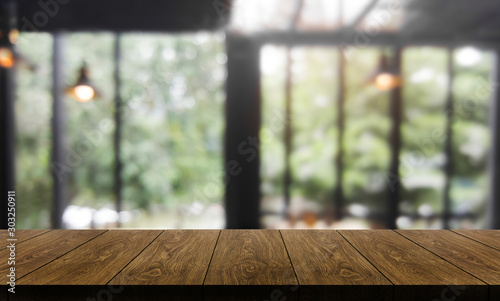 Fototapeta Wood table in blurry background of modern restaurant room or coffee shop with empty copy space on the table for product display mockup. Interior restaurant counter design concept. obraz