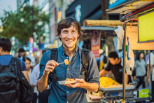 Young Man Tourist Eating Typic...