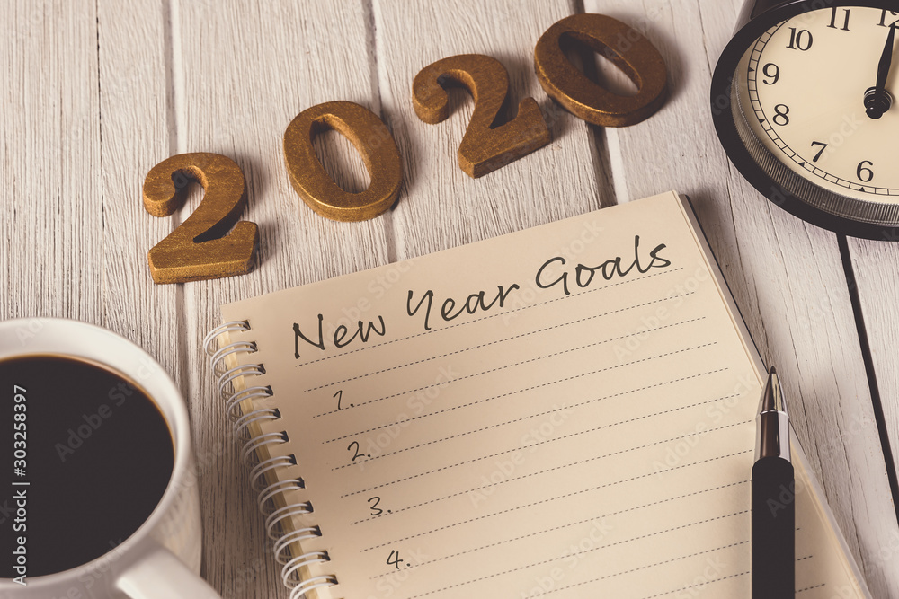New Year's Goals List written on Notebook with alarm clock, pen, coffee