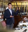 Man seller in hunting shop demonstrating shotgun