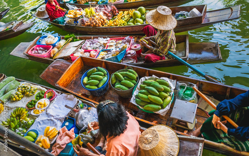Fototapeta Top view Damnoen Saduak business floating market, Fruit food on Thai tradition boat in canal, Popular famous landmark water tourist travel Bangkok Thailand, Tourism beautiful destinations place Asia obraz