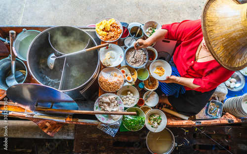 fototapeta na lodówkę Top view old woman cooking Thai noodle soup Tom Yam style on Thai tradition boat in local floating market, Famous traditional Thai street food for tourist people travel Bangkok Thailand, Tasty Asia