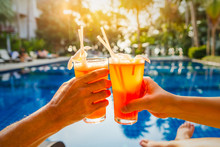 Couple Traveler Hands Holding Glass Of Cocktails On Outdoor Luxury Swimming Pool In Beach Resort Or Hotel, Cheerful Two People Enjoy On Summer Holiday Vacation, Happy Friends Drinks Toasting Celebrate
