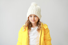 Stylish Little Girl In Winter Clothes On Light Background