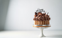 Happy Birthday Chocolate Cake With Candles And Happy Birthday Tag On White Table, Food Concept Background With Copy Space