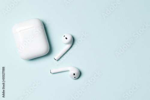 Fotografía Wireless headphones on a blue background with place for text.