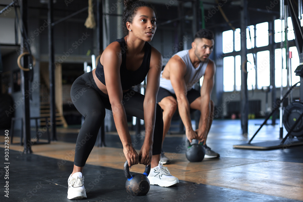 Fototapety, obrazy: Fit and muscular couple focused on lifting a dumbbell during an exercise class in a gym.