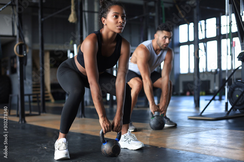 Poster Fitness Fit and muscular couple focused on lifting a dumbbell during an exercise class in a gym.