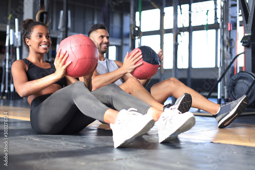 Poster Fitness Beautiful young sports couple is working out with medicine ball in gym.
