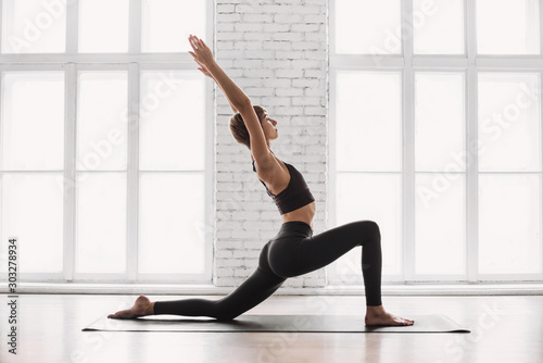 Fototapeta Young beautiful woman practicing yoga near floor window in yoga studio. Young beautiful girl doing exercises at home. Harmony, balance, meditation, relaxation, healthy lifestyle concept	 obraz
