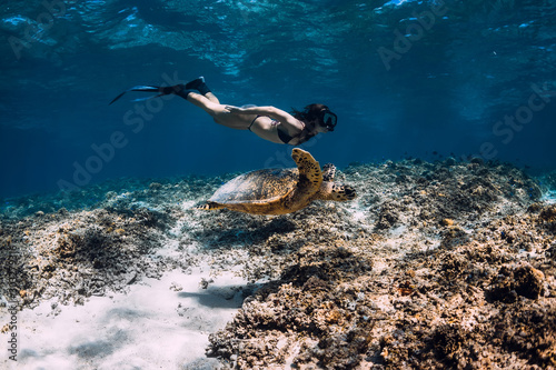 Photo  Woman freediver glides underwater with sea turtle.
