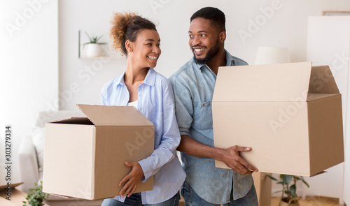 Obraz African American Spouses Carrying Moving Boxes Smiling Standing Back-To-Back Indoor - fototapety do salonu
