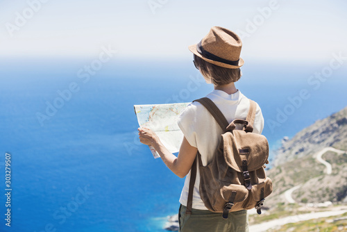 Pinturas sobre lienzo  Woman traveler with backpack holding map