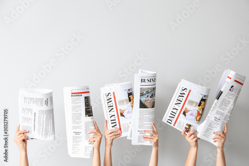 Fotografie, Obraz Female hands with newspapers on light background