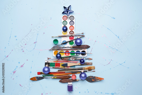 Beautiful Christmas tree made of painter tools on color background