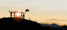 Silhouette Of Business Team Show Arm Up And Flag On Top Of The Mountain. Leadership And Success Concept.