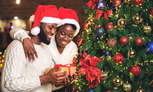 Portrait Of Happy Afro Couple Holding Gift And Standing Near Christmas Tree
