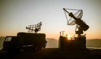 Satellite dishes or radio antennas against evening sky. Selective focus