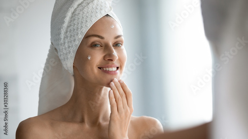 Fototapeta Smiling beautiful lady apply skincare cream look in mirror