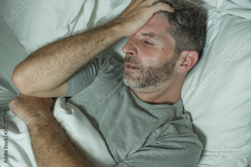 Obraz dramatic portrait of stressed and frustrated man in bed awake at night suffering insomnia sleeping disorder tired and desperate unable sleep feeling exhausted - fototapety do salonu