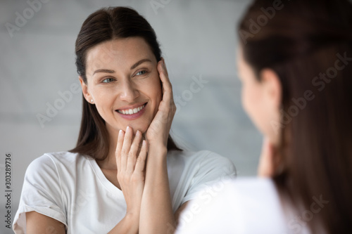 Happy beautiful young lady touching face look in bathroom mirror
