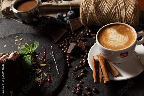 Wall Murals Cafe Coffee and desserts. Cappuccino, coffee filter holder, sprinkled with coffee beans, croissant, cheesecakes, chocolate, cheesecake, pudding and pasta on a black
