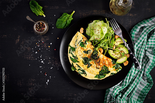 Fototapeta Ketogenic, paleo diet breakfast. Omelette with spinach and avocado, cucumber. Top view, copy space obraz