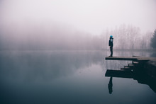 Man Standing On A Deck Above A Misty Lake. Depression And Suicide Concept.