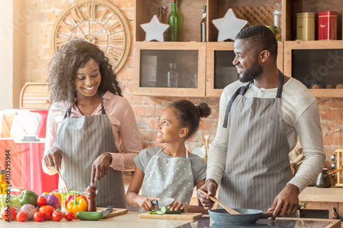 Obraz Cute little girl cutting vegetables, helping parents with dinner - fototapety do salonu