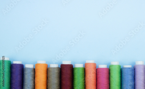Photo Multi-colored threads in spools, sewing kit, tailor's kit on a light background