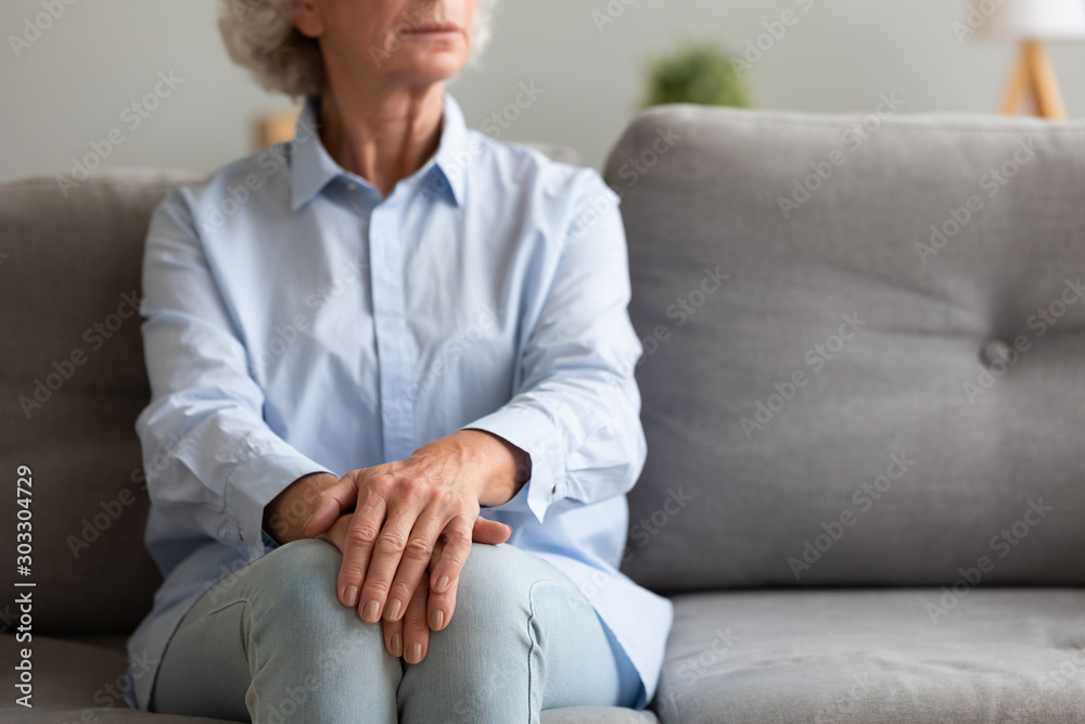 Fototapety, obrazy: Unhappy depressed senior woman sit alone on sofa, closeup view