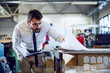 Dedicated Caucasian bearded graphic engineer in shirt and tie holding notebook and looking at sheets while standing in print shop.