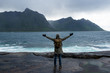 A man with backpack walking along an empty ocean beach and looking at the mountains. Fjord in Norway. Scenic view. Travel, adventure. Sense of freedom, lifestyle. Lofoten Islands, Norway. North summer