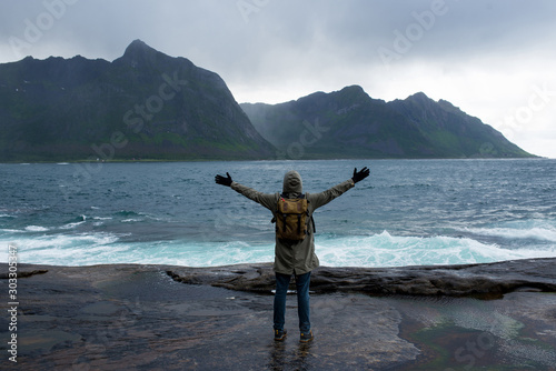 Obraz A man with backpack walking along an empty ocean beach and looking at the mountains. Fjord in Norway. Scenic view. Travel, adventure. Sense of freedom, lifestyle. Lofoten Islands, Norway. North summer - fototapety do salonu