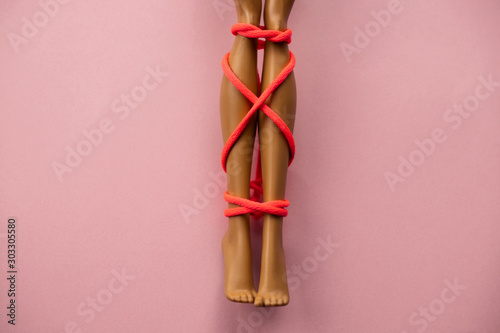 plastic doll legs tied with neon orange  rope on pink background