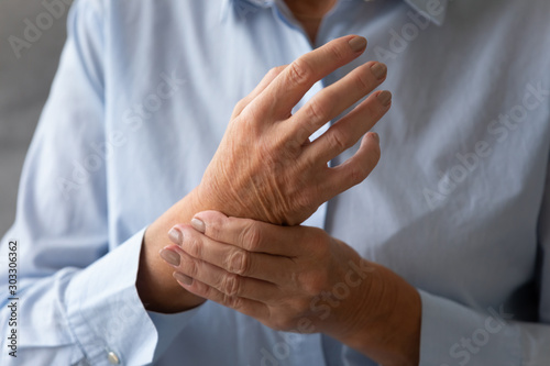 Senior lady massaging hand suffering from rheumatoid arthritis concept, closeup Canvas Print
