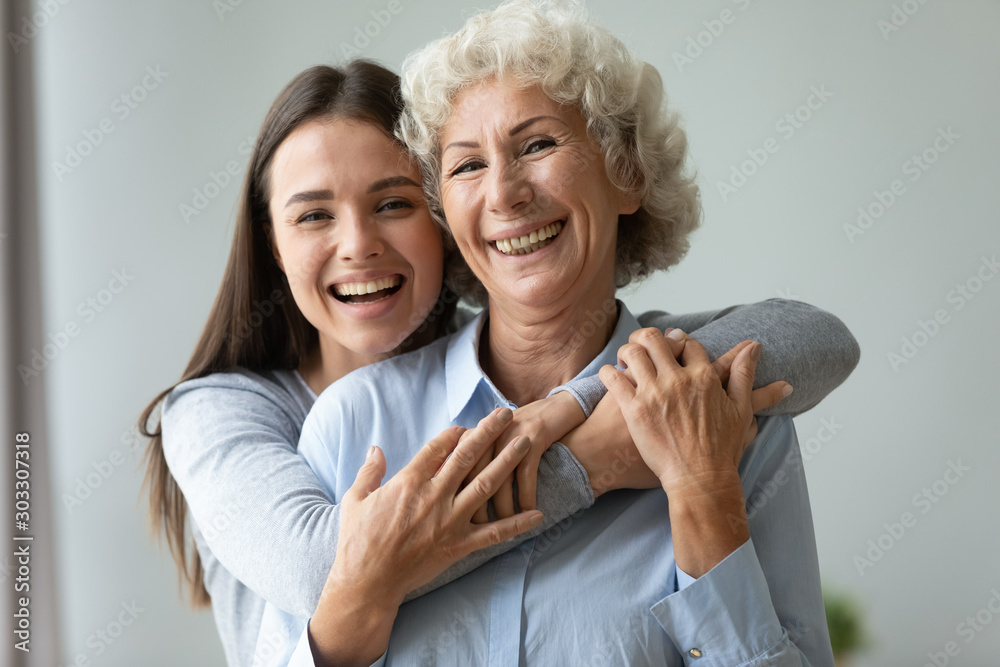 Fototapety, obrazy: Cheerful affectionate two age generation women embracing indoors, family portrait