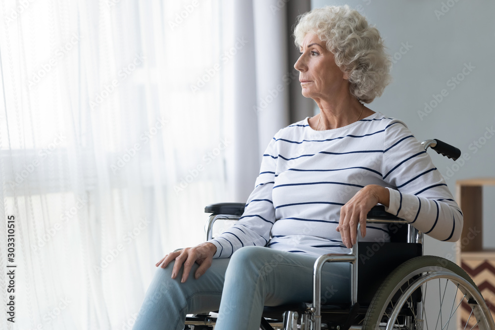 Fototapety, obrazy: Sad paraplegic old woman sit on wheelchair look through window