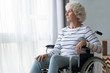 canvas print picture - Sad paraplegic old woman sit on wheelchair look through window