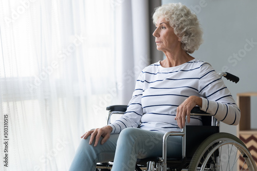 Sad paraplegic old woman sit on wheelchair look through window - 303310515