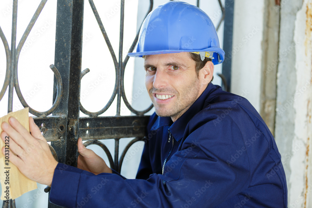 Fototapety, obrazy: tradesman using sandpaper on metal
