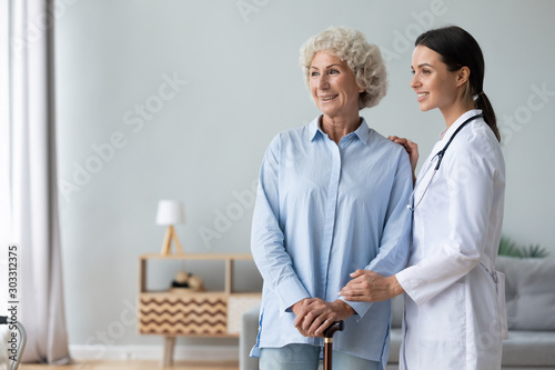 Fototapeta  Happy female doctor assisting grandma hold walking stick looking away