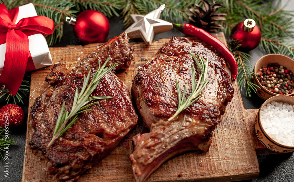 Fototapeta Christmas dinner for two, grilled beef steak ribeye, herbs and spices on a stone table with a Christmas tree and New Year's toys