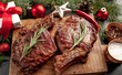 canvas print picture - Christmas dinner for two, grilled beef steak ribeye, herbs and spices on a stone table with a Christmas tree and New Year's toys