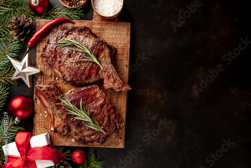 In de dag Steakhouse Christmas dinner for two, grilled beef steak, ribeye, greens and spices on a stone table with a Christmas tree and New Year's toys with copy space