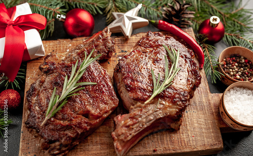 Christmas dinner for two, grilled beef steak ribeye, herbs and spices on a stone table with a Christmas tree and New Year's toys - 303312546