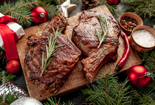 Spoed Foto op Canvas Steakhouse Christmas dinner for two, grilled beef steak ribeye, herbs and spices on a stone table with a Christmas tree and New Year's toys