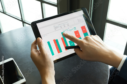 Fotografía  businessman point the finger to tablet for analysis graph visualization at coffe