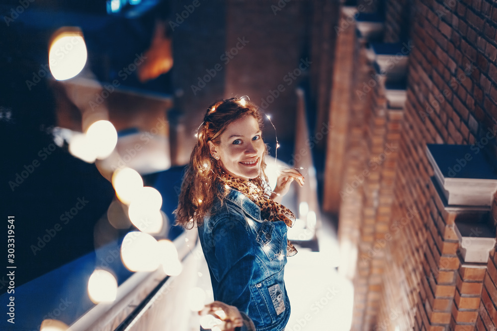Fototapety, obrazy: Happy young woman playing with fairy lights outdoors