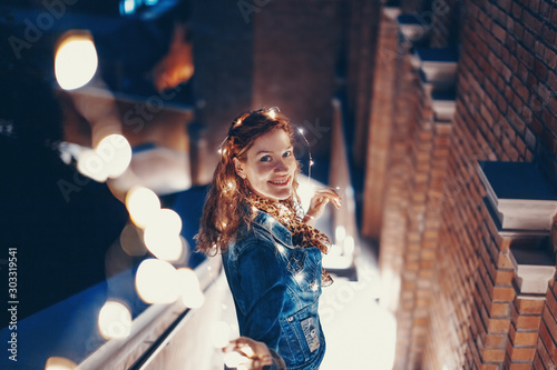 Happy young woman playing with fairy lights outdoors